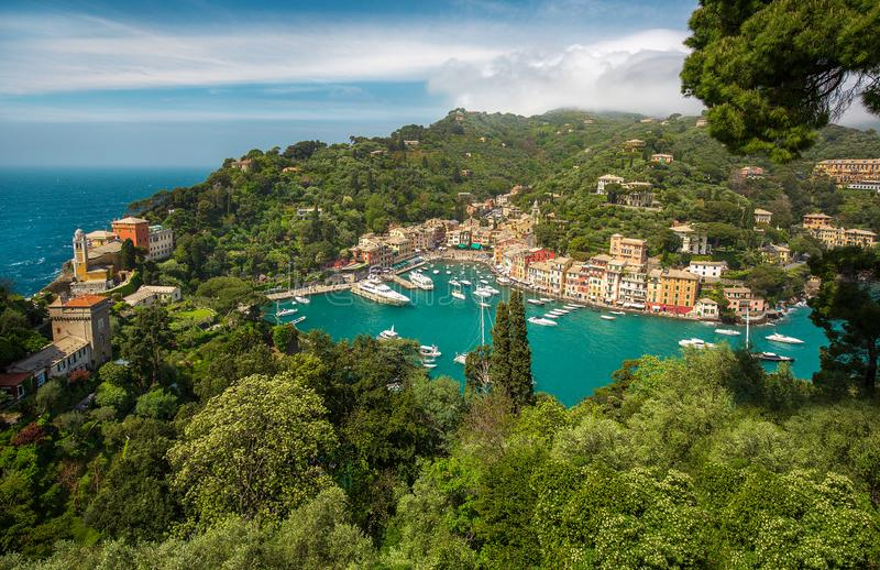 Panorama of Portofino town with multicolored houses and villas, sea and harbor bay with fishing boats and luxury yachts. On Italian riviera in Liguria, Italy stock photography