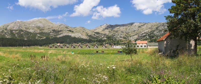 Panorama przegapia małe drewniane chałupy w Njegusi wiosce, stoi z rzędu na zielonej równinie przeciw górom na h obrazy royalty free