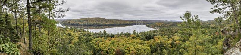 Panorama que mira hacia fuera sobre un lago rodeado por el bosque en otoño foto de archivo libre de regalías
