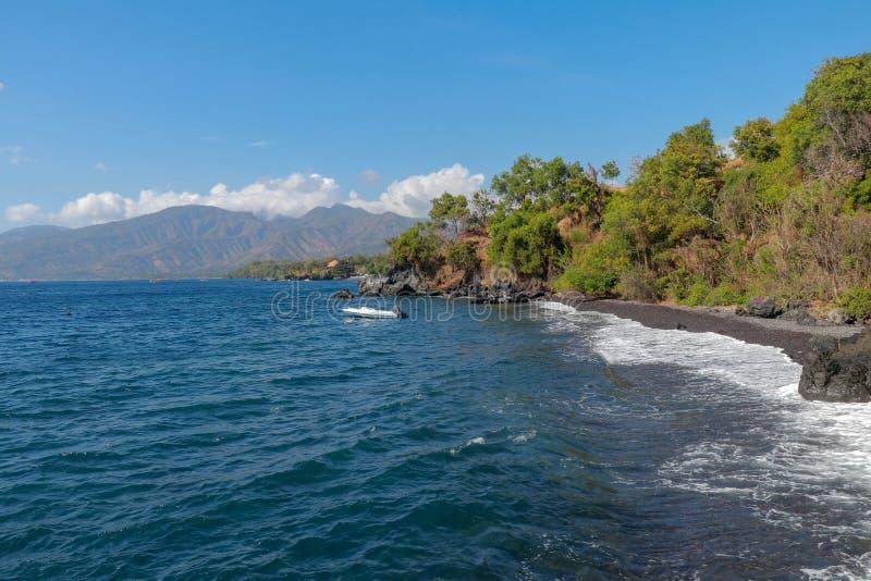 Panorama que negligencia a praia tropical, Bali, Indonésia Ondas das mostras que discordam contra uma praia preta vulcânica bonit imagens de stock