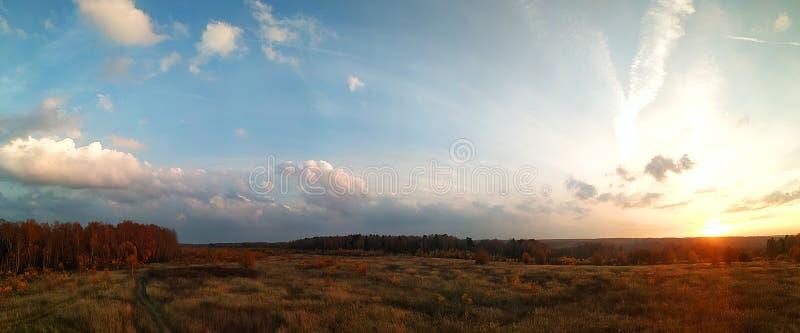 Panorama que sorprende del paisaje rural del otoño de un pueblo europeo con un cielo colorido y un campo de oro infinito fotos de archivo