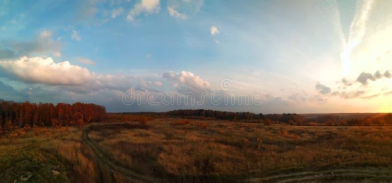 Panorama que sorprende del paisaje rural del otoño de un pueblo europeo con un cielo colorido y un campo de oro infinito imagen de archivo libre de regalías