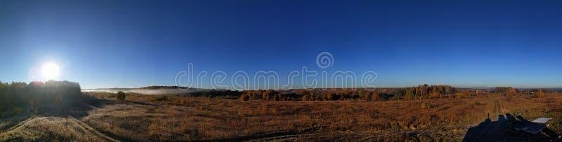 Panorama que sorprende del paisaje rural del otoño de un pueblo europeo con un cielo colorido y un campo de oro infinito fotos de archivo libres de regalías