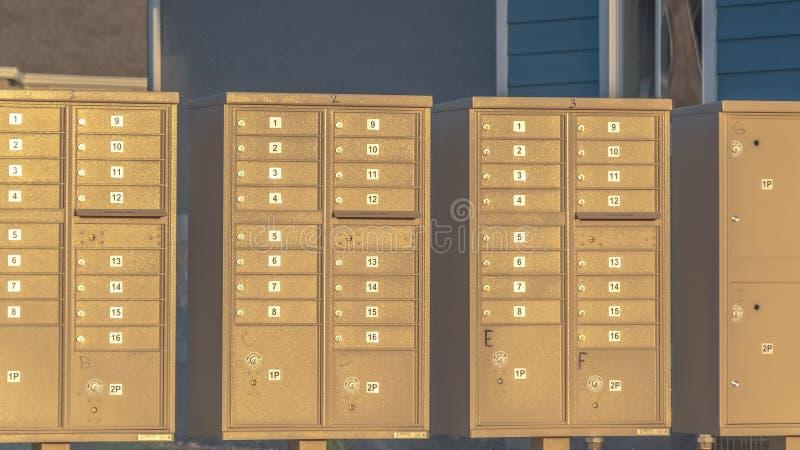 Panorama Rangée de boîtes aux lettres avec numéros et compartiments à côté d'une route par jour ensoleillé image libre de droits