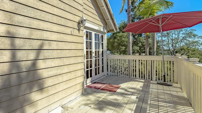 Panorama Red umbrella at the corner of the balcony of a house with wooden exterior wall. Lush trees can be seen against the clear blue sky on this sunny day royalty free stock images