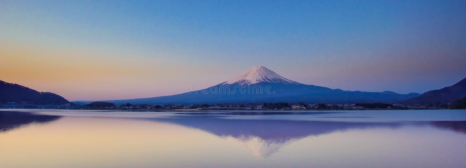 Reflection of Fuji mountain with snow capped and the Moon in the morning Sunrise at Lake kawaguchiko, Yamanashi, Japan. Panorama Reflection of Fuji mountain with stock photography