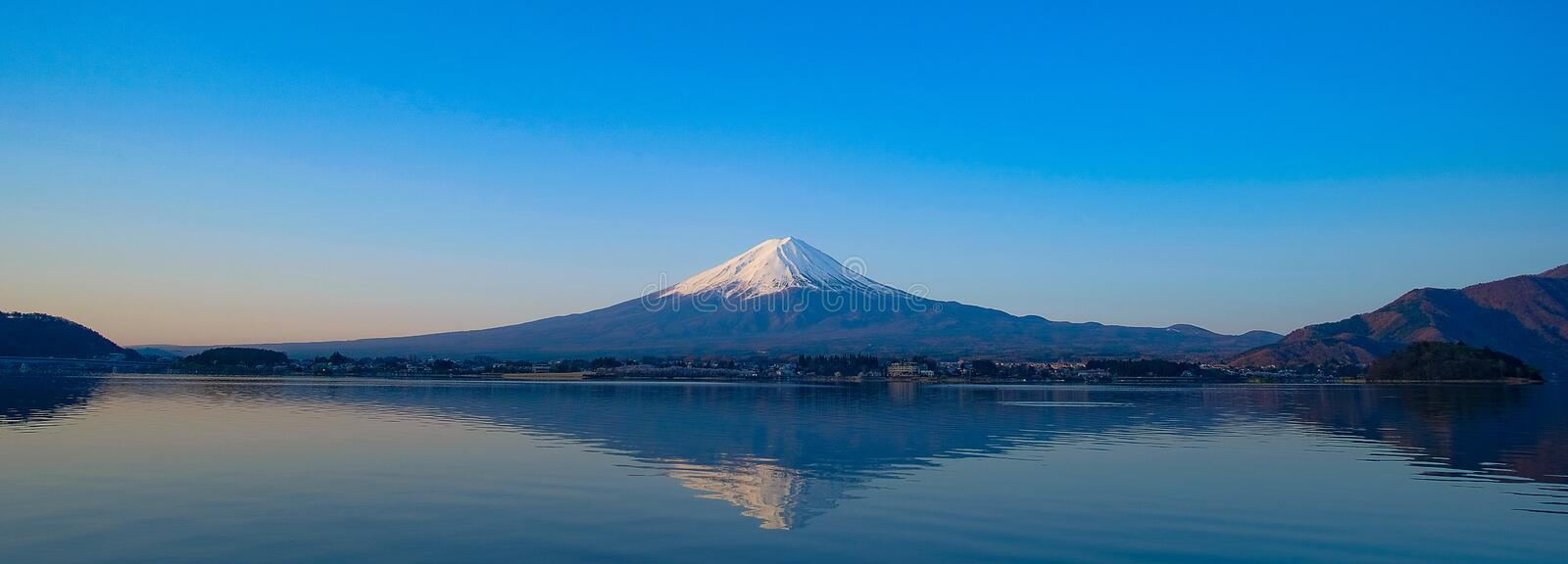 Panorama Reflection of Fuji mountain with snow capped in the morning Sunrise at Lake kawaguchiko, Yamanashi, Japan royalty free stock images