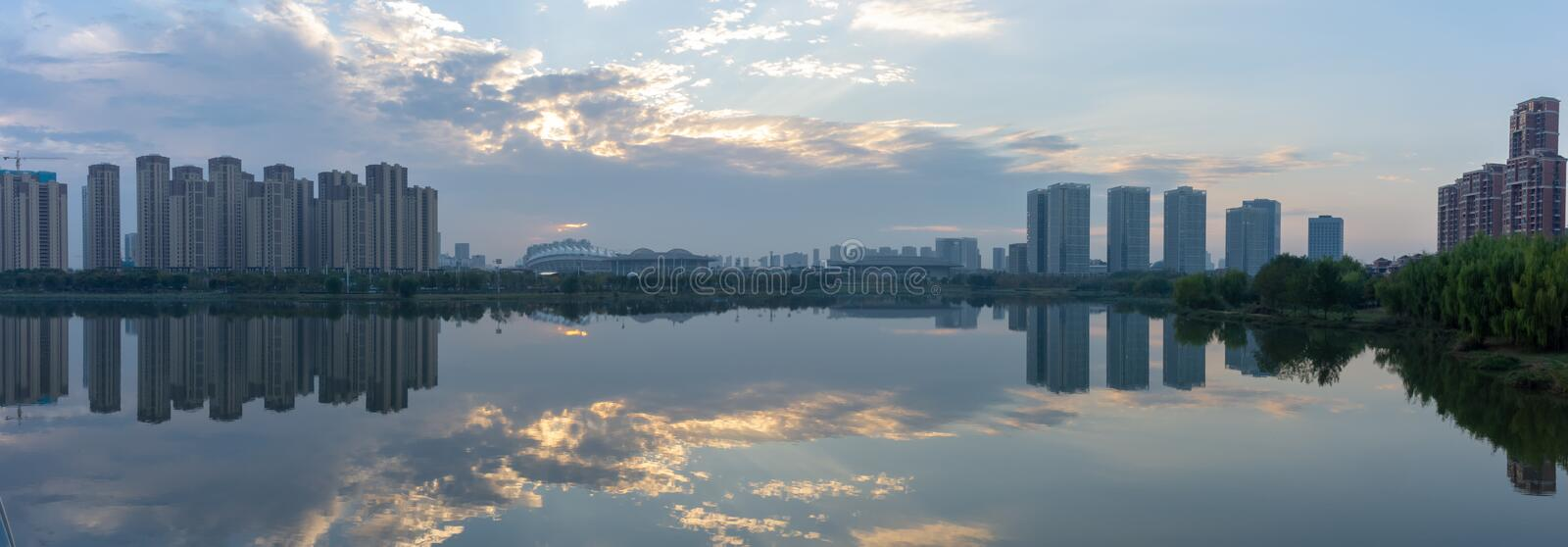 A panorama reflective evening shot of trees and buildings. In Wuhan, China on an unusually low pollution day stock photo