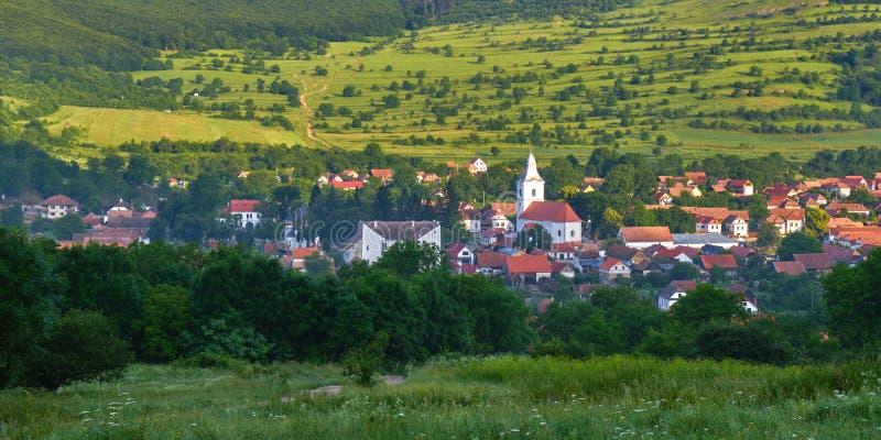 Panorama: Rimetea village Torocko in Hungarian or Eisenmarkt, Eisenburg, Traschen in German with white church and houses. Panorama: Rimetea village Torocko in stock photo