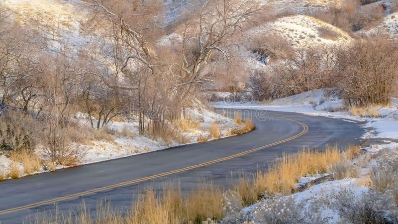 Panorama Road and homes on sunlit snowy mountain in winter. Road curving through the snowy mountain in Salt Lake City on a sunny winter day. Homes and blue sky royalty free stock photography