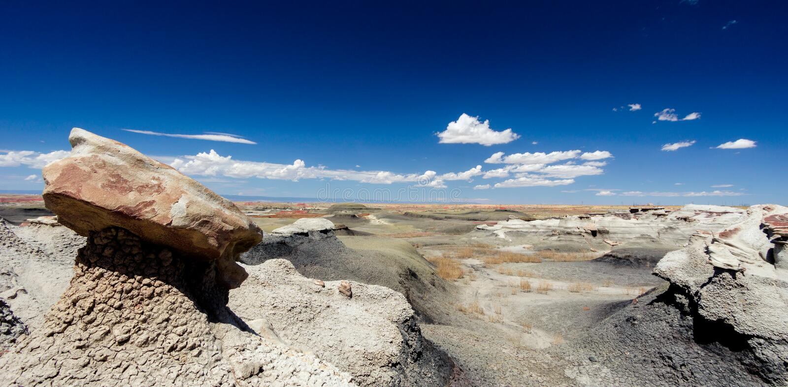 Panorama rock desert landscape in northern New Mexico. In the Bisti/De-Na-Zin Wilderness Area with washed out hoodoo rock formations under a blue sky stock photography