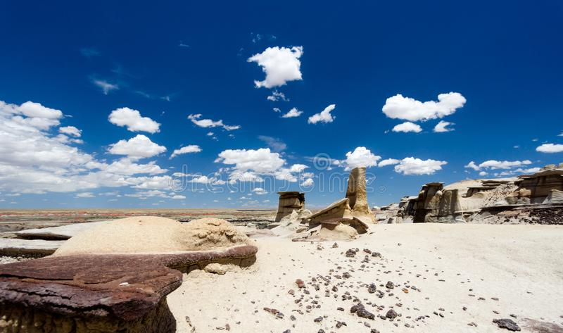 Panorama rock desert landscape in northern New Mexico. In the Bisti/De-Na-Zin Wilderness Area with washed out hoodoo rock formations under a blue sky stock images