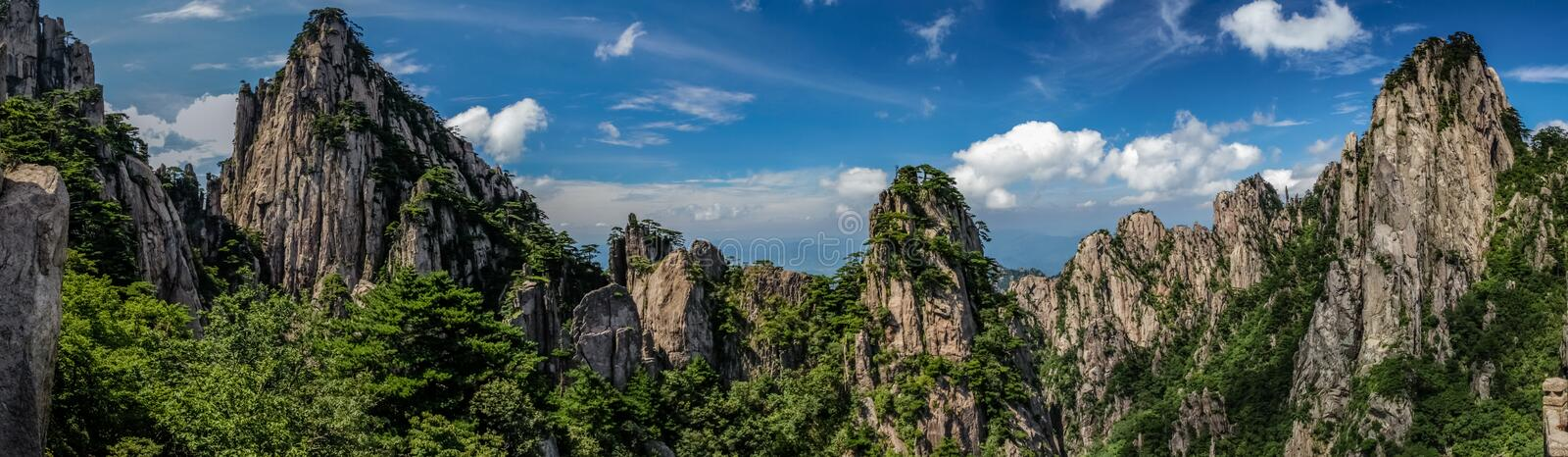 Panorama of rocky peaks and old pine trees cover the mountains under a bright blue sky with whispy clouds in Huangshan China stock photo