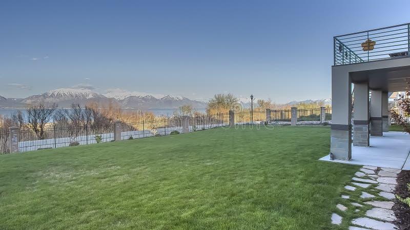 Panorama Ruime yard van huis met mening van meer en sneeuwberg onder blauwe hemel stock fotografie