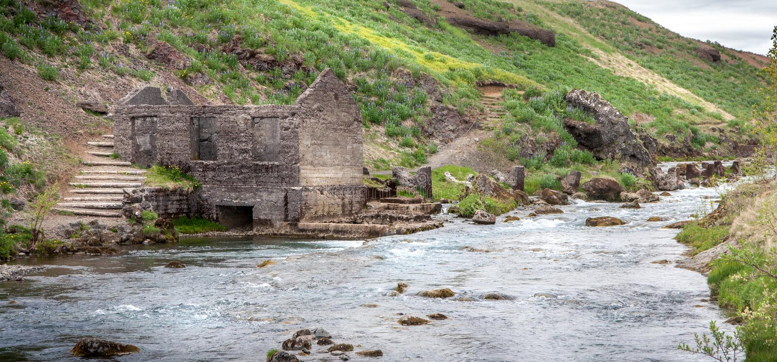 Panorama of the ruins of an old stone mill standing by the rapids of the river royalty free stock image