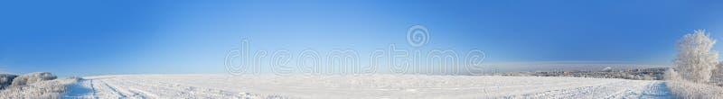 Panorama rurale con un campo, neve, foresta, città del paesaggio di inverno immagine stock