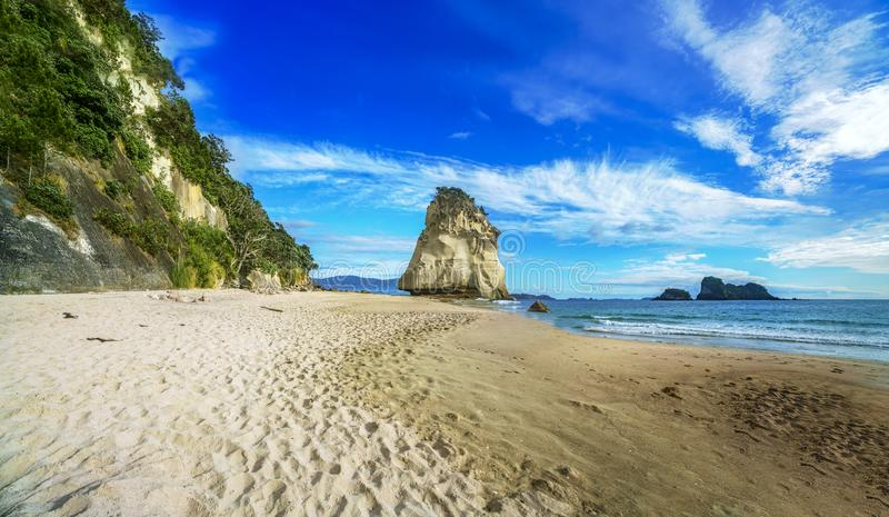Panorama of sandstone rock monolith at cathedral cove,coromandel, new zealand. Mighty sandstone rock monolith in the water of cathedral cove beach,coromandel royalty free stock image