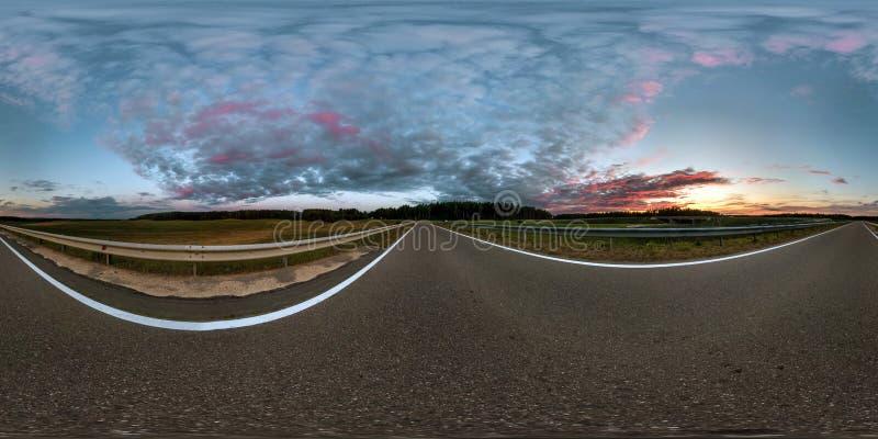 Panorama sferico senza cuciture completo 360 gradi di vista di angolo sulla strada asfaltata fra i campi nel tramonto di sera di  fotografia stock libera da diritti