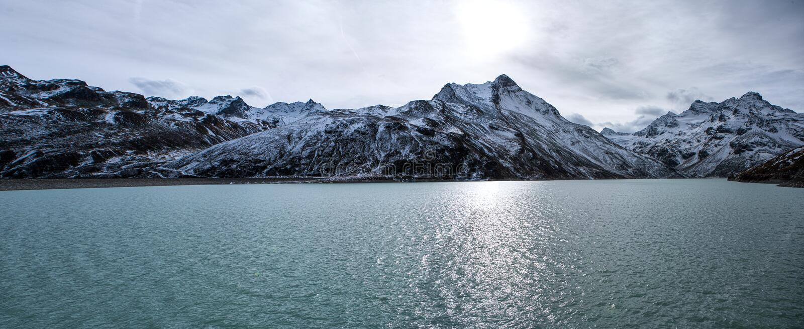Panorama shot in the alps in autumn with snowy mountains in the background and water of the silvretta dam in the foreground. Panorama shot in the alps in autumn stock photography