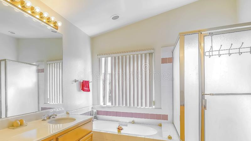 Panorama Shower stall built in bathtub and vanity with double sink inside a bathroom. The room is well lighted by light bulbs above the mirror and sunlight stock photography