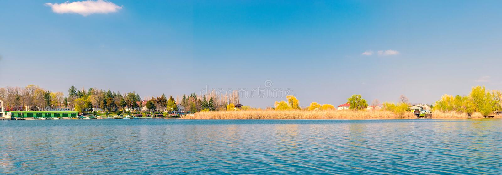 Panorama showing lake water, reed island and boat peer wit copy space royalty free stock photo