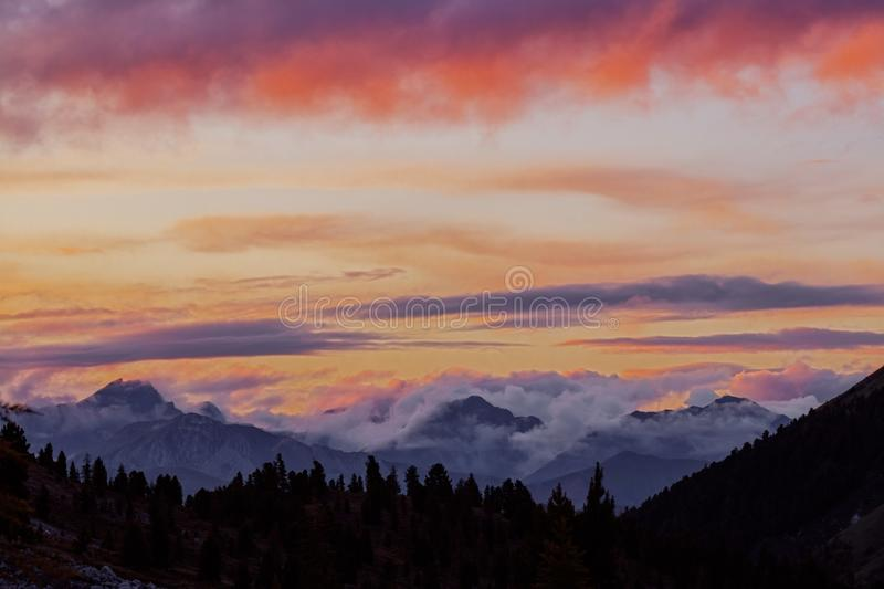 Panorama silhouette forest and mountain tops in red orange blue clouds gradient sunset stock photos