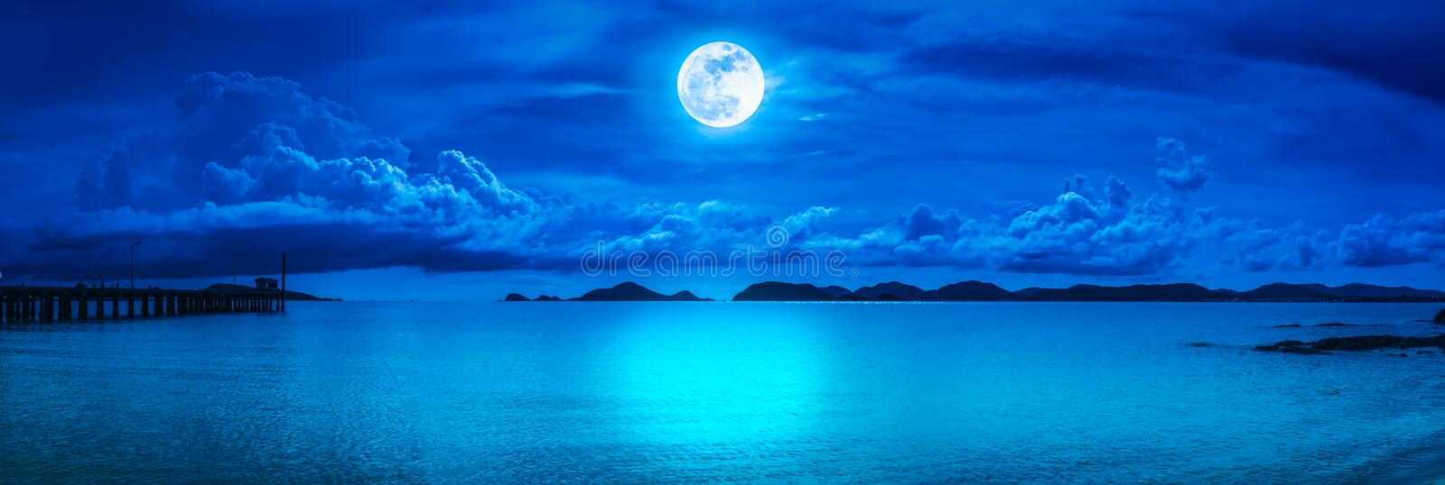 Panorama of sky with full moon on seascape to night. Beautiful panorama view of the sea. Colorful blue sky with cloud and bright full moon on seascape to night stock photo