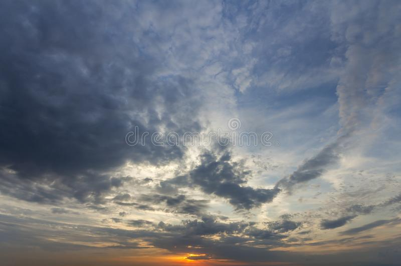 Panorama of sky at sunrise or sunset. Beautiful view of dark blue clouds lit by bright orange yellow sun on clear sky. Beauty and stock photos