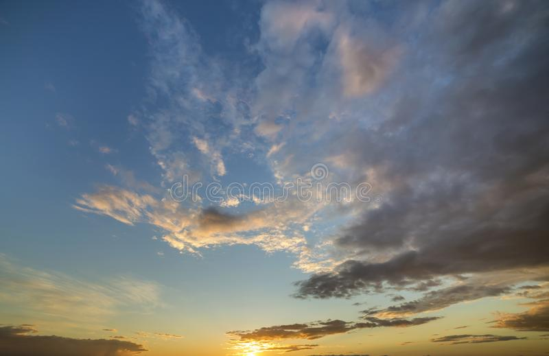 Panorama of sky at sunrise or sunset. Beautiful view of dark blue clouds lit by bright orange yellow sun on clear sky. Beauty and royalty free stock photos