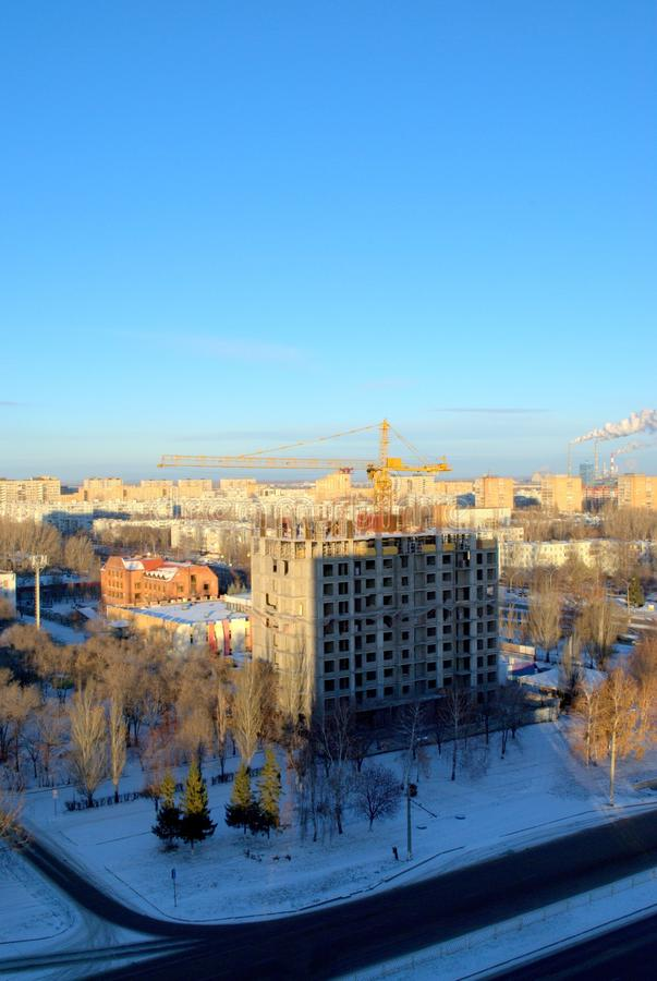 Panorama of a snow-covered city with a view of the tower crane and a high-rise residential building under construction. The shot was taken from the height of royalty free stock photography