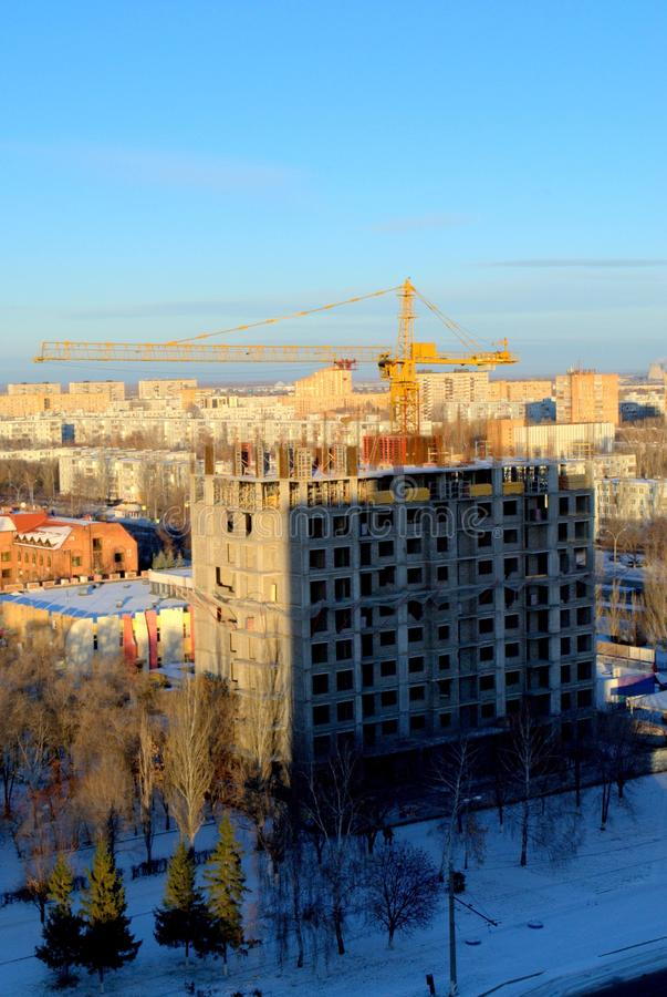 Panorama of a snow-covered city with a view of the tower crane and a high-rise residential building under construction. The shot was taken from the height of royalty free stock photo