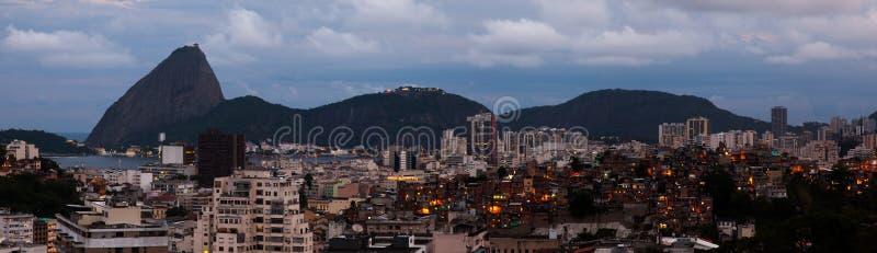 Panorama- socker släntrar och favelaen på skymning - Rio de Janeiro royaltyfri bild