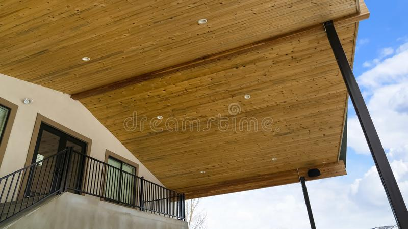 Panorama spód dach z brąz drewnianymi deskami i round podsufitowymi światłami przeciw niebu obrazy royalty free
