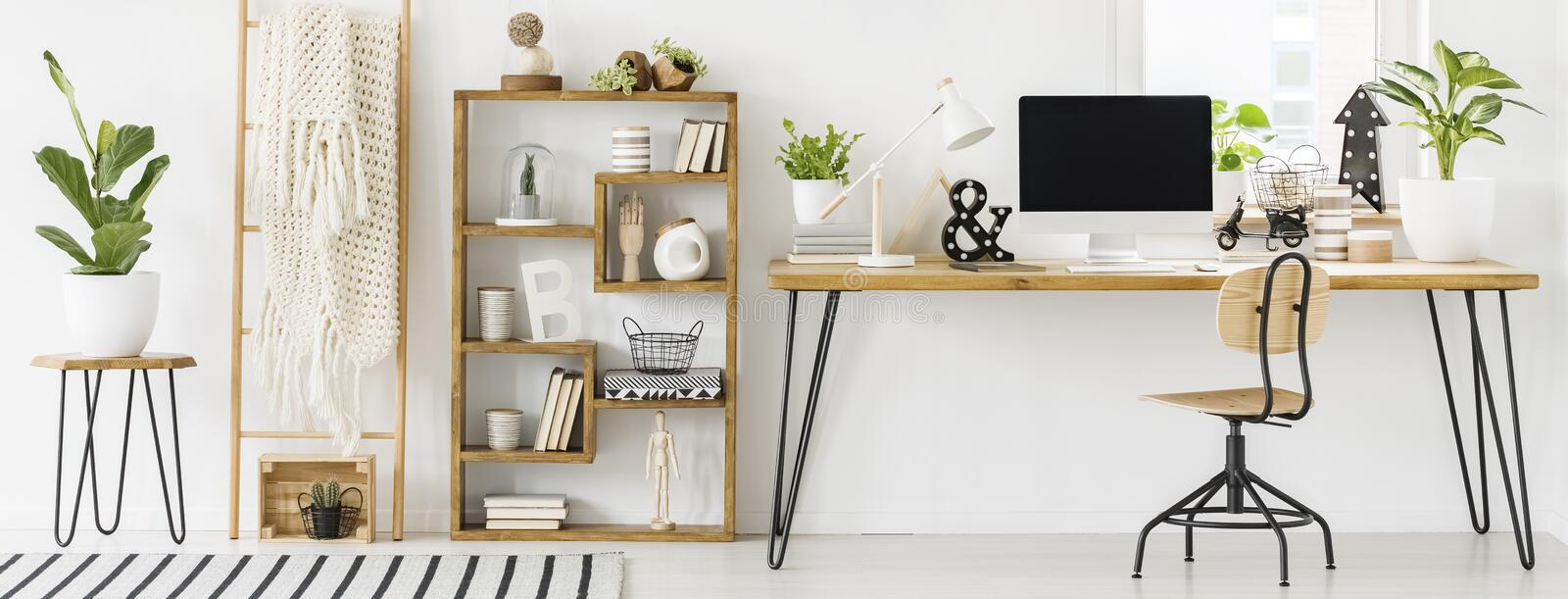 Panorama of a spacious home office interior with a bookcase with. Decorations next to a desk with a computer and white lamp. Real photo stock photo