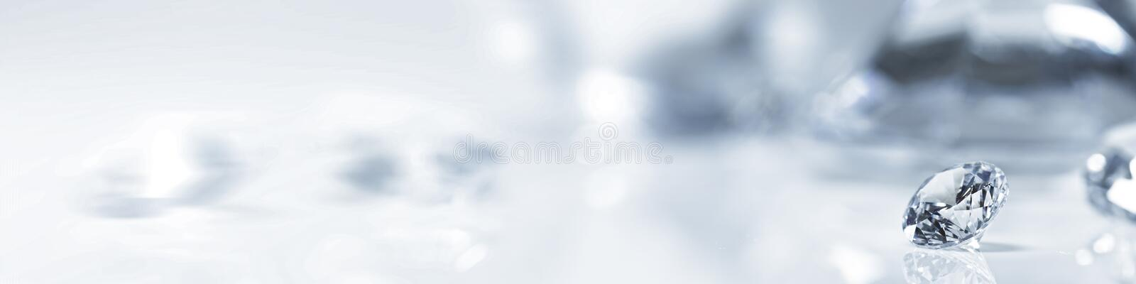 Still with expensive diamonds in front of a white background. Panorama still with expensive cut diamonds in front of a white background, reflections on the royalty free stock photography