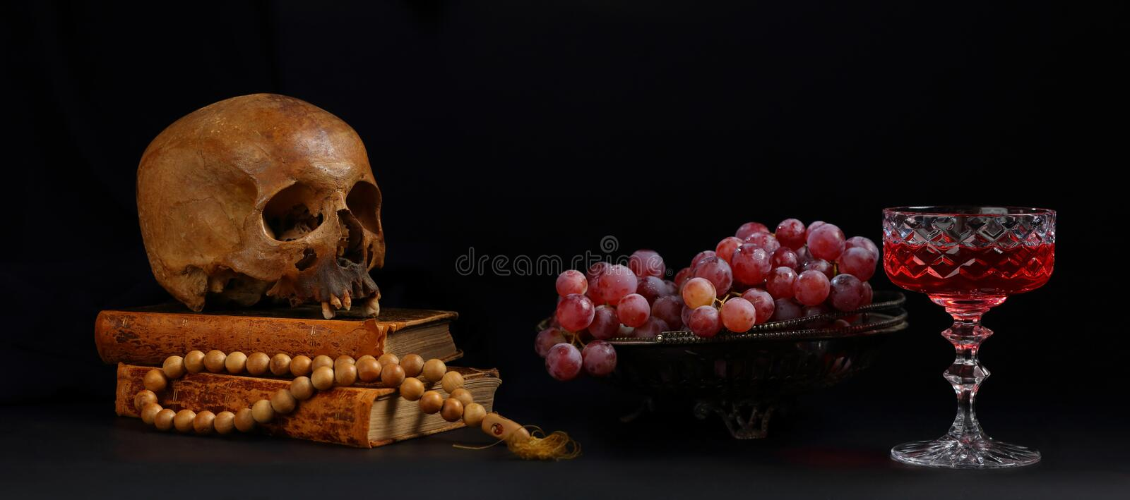 Still life with a skull, a vase of grapes and a glass of red wine stock photo