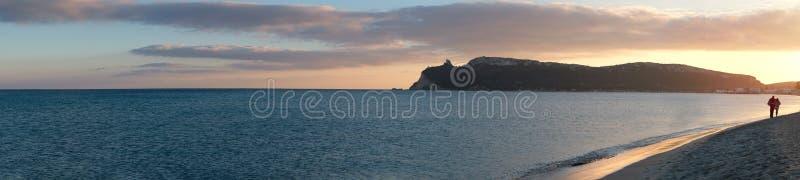 panorama superbe de la plage principale de Cagliari (poetto sella del diavolo) avec deux amants de marche au coucher du soleil sa image stock