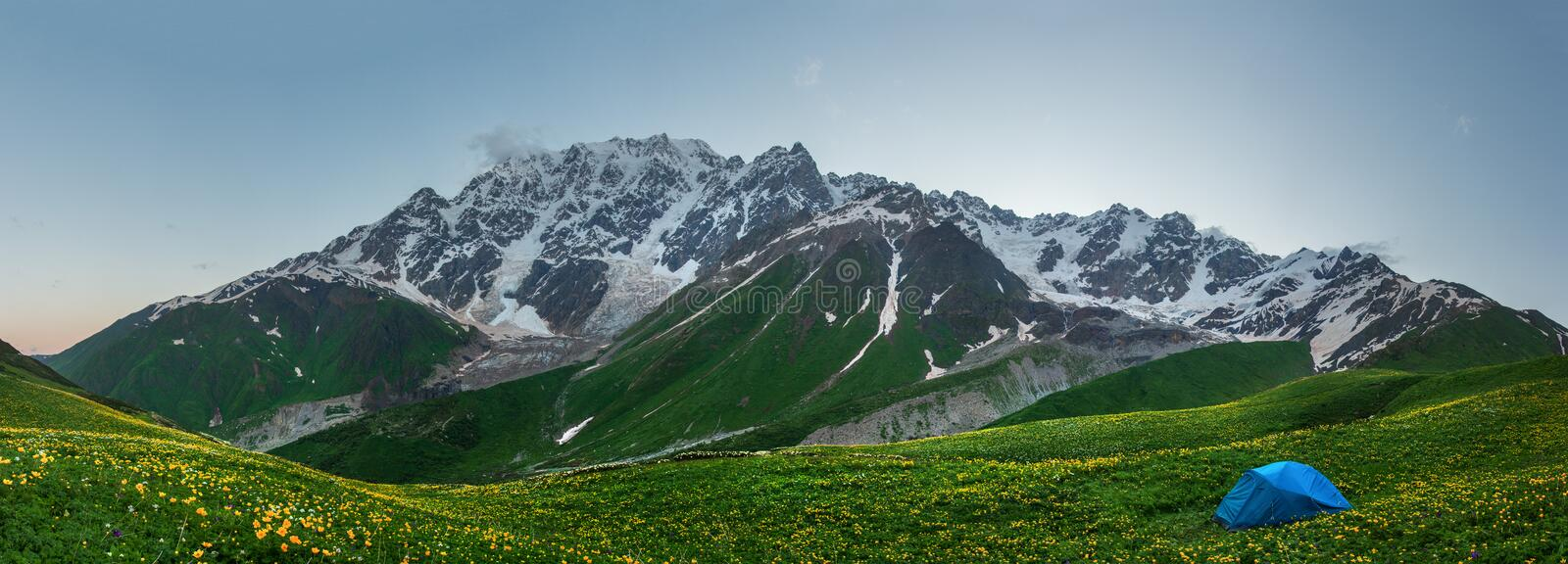 Panorama Svaneti mountains in Georgia. Landscape of Caucasus mountain range. Scenic mountains with tent in tourist camp stock images