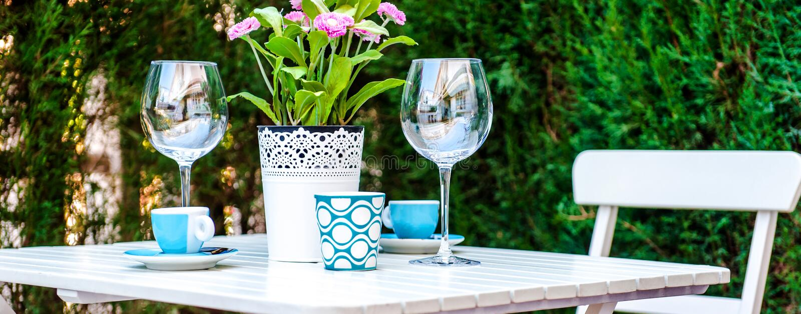 Panorama table setting with a wine glasses, cups and flowers in a pot royalty free stock photos
