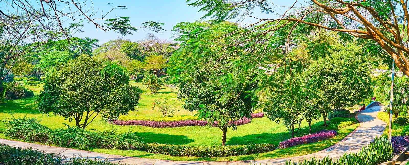 Panorama of Theingottara park, Yangon, Myanmar. Panorama of Theingottara park with shady alleys, juicy lawn, ornamental flower beds and tall spread trees, Yangon royalty free stock photography