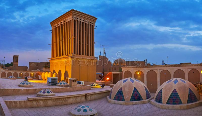 The stained-glass domes of Tehraniha House, Yazd, Iran. Panorama with traditional badgir windcatcher and tiny domes with stained-glass decor on the roof of royalty free stock photos