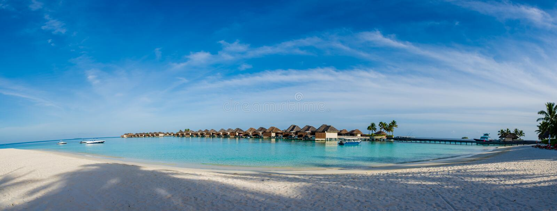Panorama tropical bonito surpreendente da praia de bungalos da água perto do oceano com as palmeiras sob o céu azul em Maldivas imagem de stock