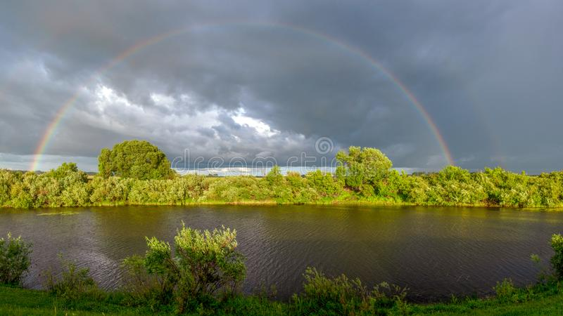 Panorama of two large rainbows in the rain. royalty free stock photos