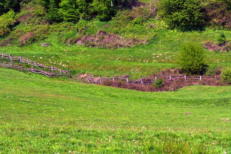 Mountain and valley, alpine meadow with fence. stock images