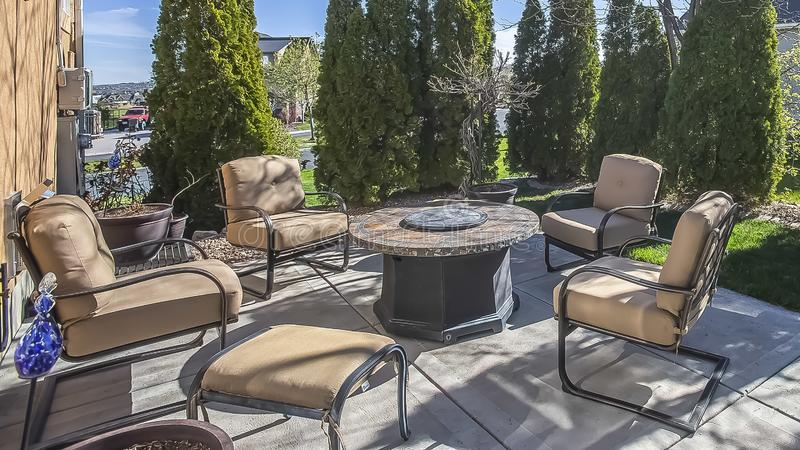 Panorama Upholstered metal chairs and round table at the patio of a home under blue sky royalty free stock photo