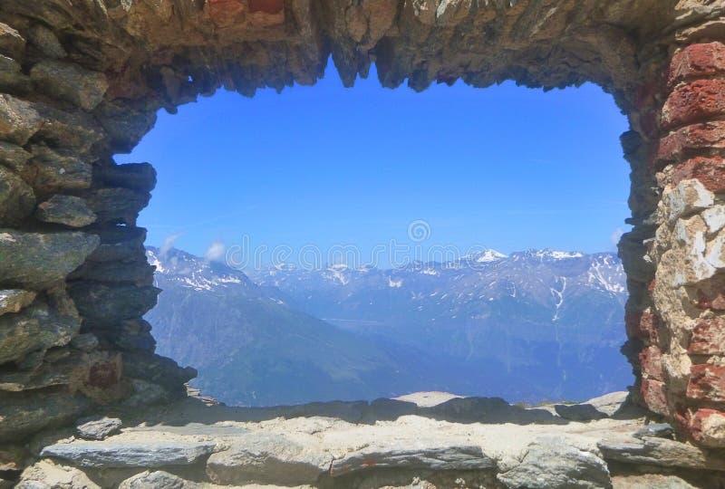 Panorama van bergen door een venster van bakstenen royalty-vrije stock afbeelding