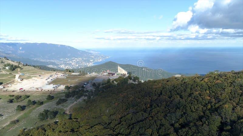 Panorama van bergen met groen bos, met een moderne Europese stad op de kust van het Overzees die op schoon worden behandeld stock foto