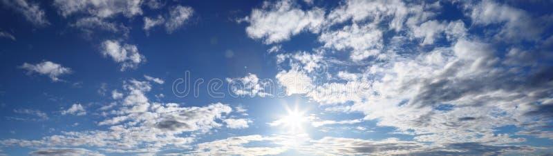 Panorama van blauwe hemel met zon en wolken stock afbeeldingen