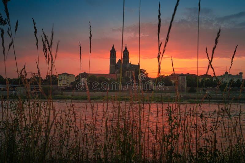 Panorama van bloedige zonsondergang voor kathedraal in Maagdenburg en rivier Elbe, Duitsland, de Zomer stock foto's