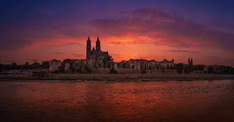 Panorama van bloedige zonsondergang voor kathedraal in Maagdenburg en rivier Elbe, Duitsland, de Zomer royalty-vrije stock foto's